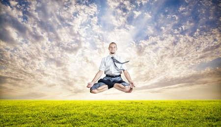 dhyana: Businessman doing Yoga meditation and levitating under the green grass at sunset sky