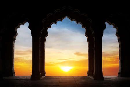 극적인 오렌지 일몰 하늘 배경에서 오래 된 사원 인도 아치 실루엣. 텍스트에 대 한 여유 공간 스톡 콘텐츠