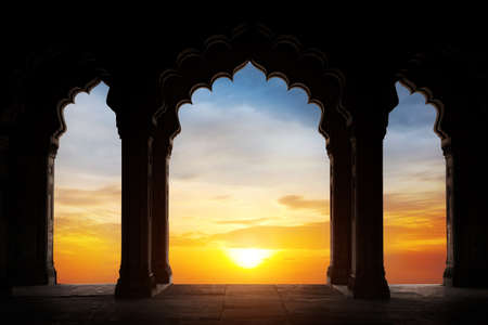 Indian arch silhouette in old temple at dramatic orange sunset sky background. Free space for text Фото со стока