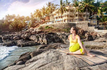 kovalam: Yoga by woman in yellow costume on the stone nearby ocean and tropical resort in Kovalam, Kerala, India