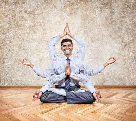 paz interior: Feliz hombre de negocios indio con muchas manos que hace yoga en la oficina Foto de archivo