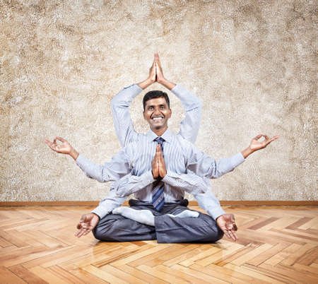 dhyana: Happy Indian businessman with many hands doing yoga in the office