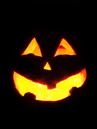 Scary Halloween pumpkin face glowing inside at black background photo