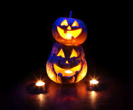 Scary Halloween pumpkins with eyes glowing inside at black background photo