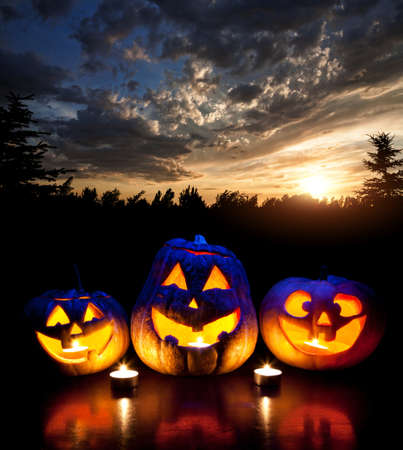 Halloween pumpkins glowing inside at forest and sunset evening sky background photo