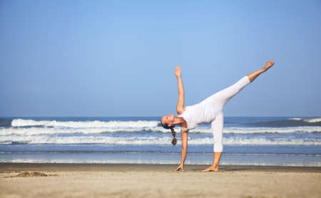 Yoga half-moon pose by woman in white costume on the beach near the ocean in India