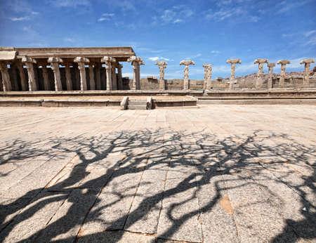mystic place: Ancient ruins of Vijayanagara Empire near Vittala Temple at blue sky and shadow from the tree in Hampi, Karnataka, India