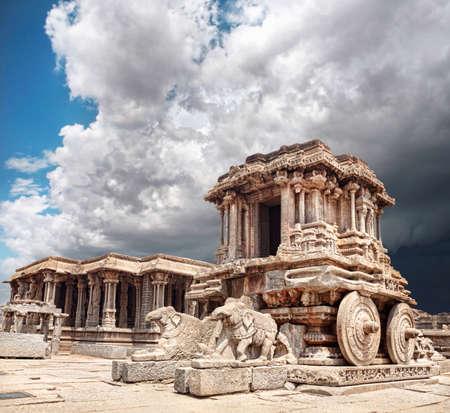 karnataka: Carro de piedra en el patio del Templo Vittala en el cielo nublado azul en Hampi, Karnataka, India