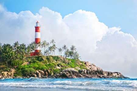 kovalam: Lighthouse on the rocks near the ocean at blue sky with big white clouds in Kovalam, Kerala, India