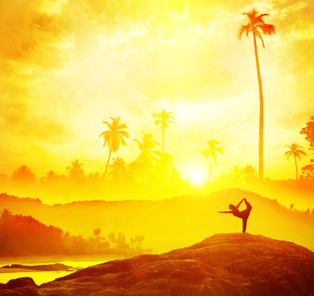 Woman silhouette doing Yoga in tropics near the sea at sunset in India photo