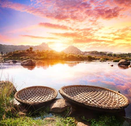 Round shape boats on Tungabhadra river at sunset sky in Hampi, Karnataka, India