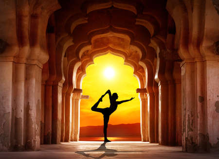 india people: Man silhouette doing yoga in old temple at orange sunset sky background