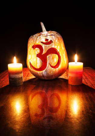 Halloween pumpkin with carved Om symbol glowing inside and candles nearby at black background