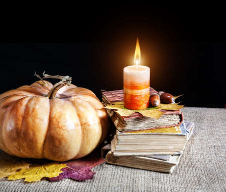 Pumpkin and heap of old books with candle on it at black background. Free space for your text photo
