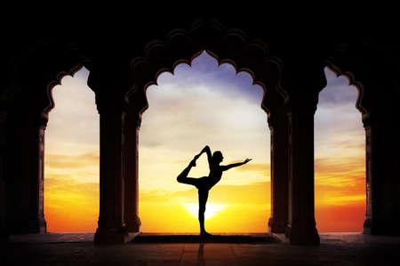 Man silhouet doet yoga in oude tempel bij oranje zonsondergang hemel achtergrond Stockfoto