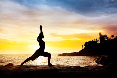 yoga rocks: Woman doing Yoga warrior pose in silhouette on the cliff near lighthouse at sunset sky in Kovalam, Kerala, India Stock Photo