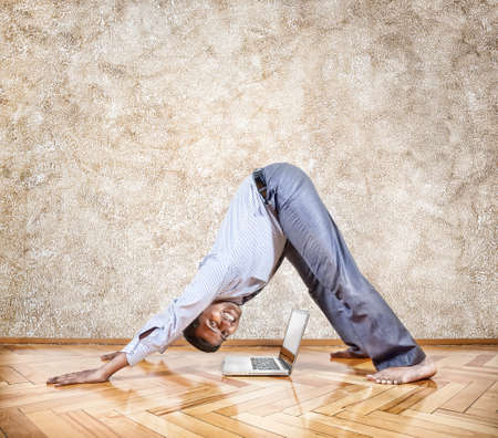 Happy Indian businessman doing yoga near the laptop in the office  photo