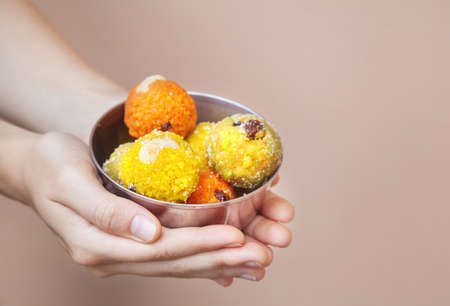Woman holding Indian traditional sweets ladu in metal bowl at black background