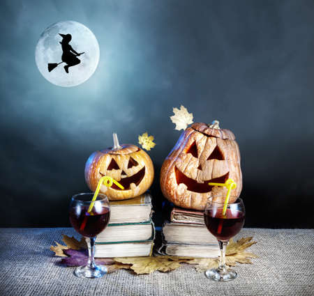 Halloween pumpkins drinking wine on the heap of books and witch silhouette on the broom flying near the full moon at dark background photo