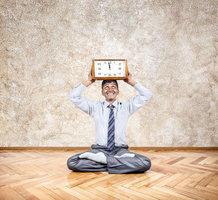 Happy Indian businessman holding big clock in meditation pose in the office Stock Photo - 21461147