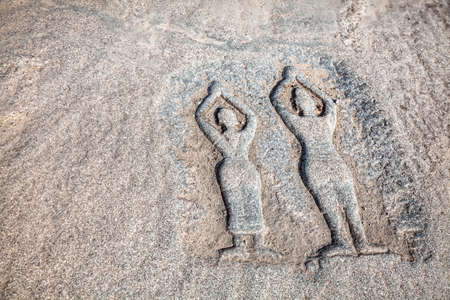 ancient yoga: Ancient stone with carved figure of people doing yoga in Hampi, Karnataka, India
