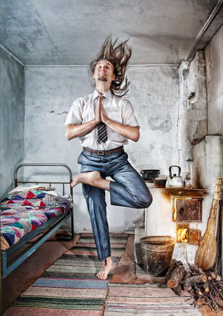 Peaceful Businessman with hair up doing yoga and meditate in old Russian house with traditional stove photo