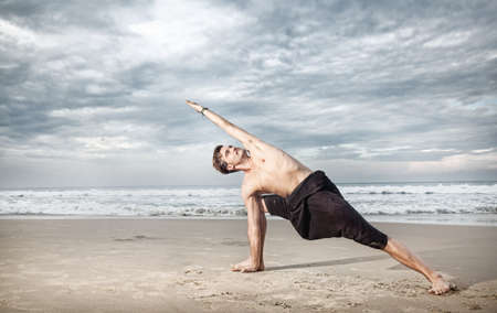 Yoga utthita parshvakonasana pose by man in black trousers on the beach near the ocean in India photo