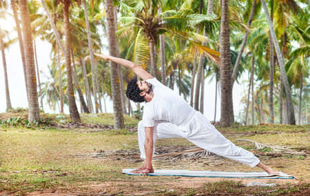 meditative: Yoga by happy Indian man in white trousers near palm trees in Kerala, India Stock Photo