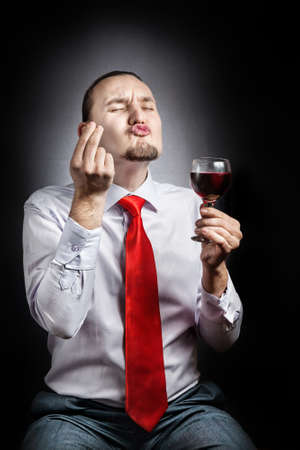 Man with beard in red tie testing the glass of red wine and gesturing at black background Stock Photo