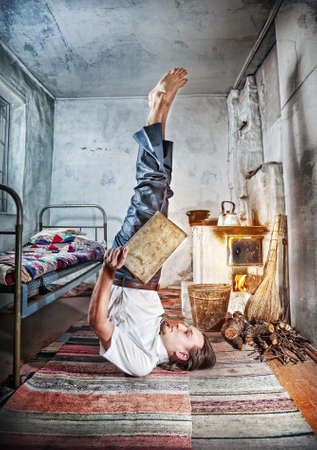 Businessman doing yoga and reading the book in old Russian house with traditional stove photo