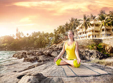Woman doing yoga meditation in yellow costume on the stone nearby ocean and tropical resort in Kovalam, Kerala, India