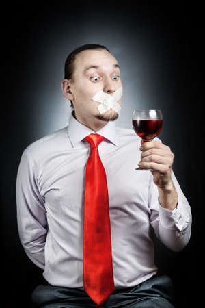 outcry: Man in red tie with plaster on his mouth holding the glass of red wine at black background. Represents outcry alcoholic dependency Stock Photo