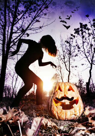 Halloween pumpkin with moustache and silhouette of witch in the dark forest photo
