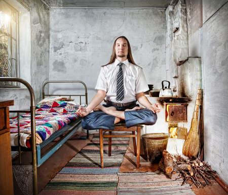 meditation room: Businessman with long hair doing meditation in old Russian house with traditional stove