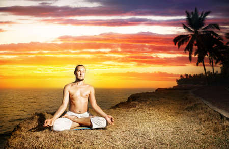 Yoga meditation in lotus pose by man in white trousers on the cliff near the ocean at sunset in Kerala, India photo