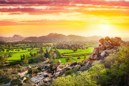 valley of the temples: View to Rice plantation from top of Hanuman monkey temple on hill at sunset in Hampi, Karnataka, India