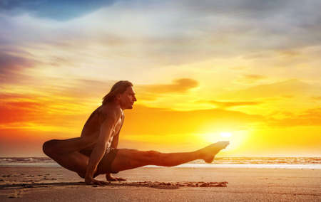 Man doing Yoga on the beach near the ocean in India photo