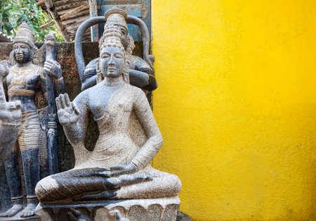 mamallapuram: Stone Buddha statue near yellow wall in Mamallapuram, Tamil Nadu, India