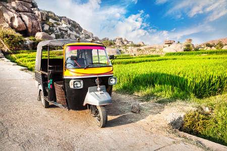 karnataka: Indian auto rickshaw y arroz plantaci�n cerca de Hanuman templo de los monos en el cielo azul en Hampi, Karnataka, India Foto de archivo