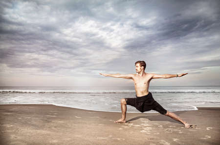 yoga pants: Yoga warrior pose by man in black trousers on the beach near the ocean in India