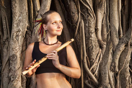 Woman with bamboo Indian flute Bansuri near banyan tree in Goa, India photo