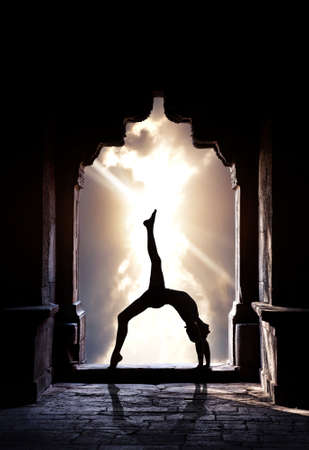 Man silhouette doing yoga in old temple at sunset sky photo