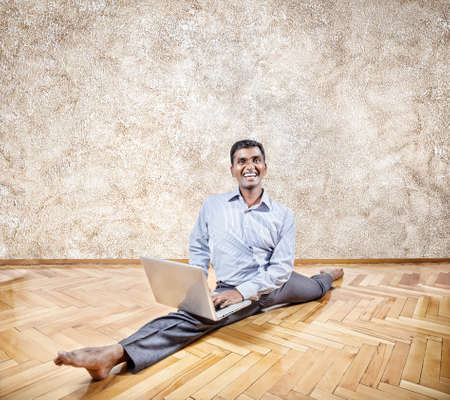 indian yoga: Happy Indian businessman doing yoga with laptop in the office