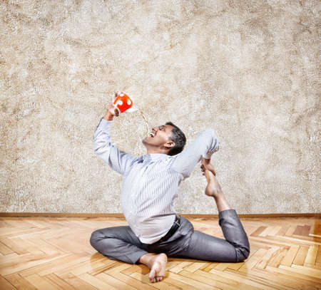 Indian businessman in pigeon pose drinking tea from red teapot in the office photo