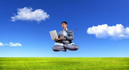 levitation: Businessman with laptop levitating in lotus pose under the grass at blue sky with white clouds Stock Photo