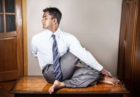 pause: Indian businessman doing yoga on the table in the office  Stock Photo