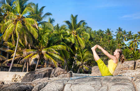 kovalam: Yoga by woman in yellow costume on the stone at tropical palm trees background in Kovalam, Kerala, India