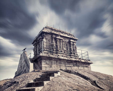 mamallapuram: Ancient temple at dark dramatic sky with crow nearby in Mamallapuram, Tamil Nadu, India Stock Photo