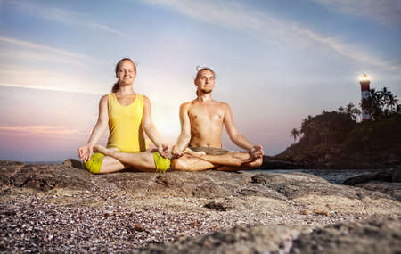 Couple doing meditation in lotus pose on the stone near the sea at lighthouse background in Kovalam, Kerala, India photo