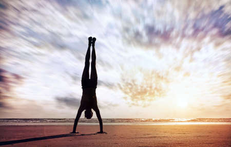 Handstand yoga pose by man silhouette on the beach near the ocean in India